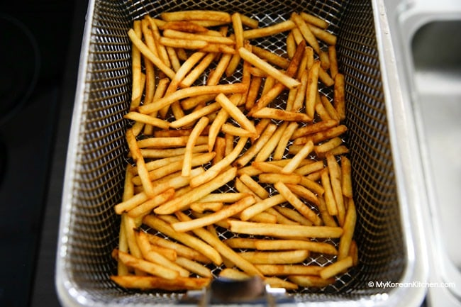 Deep fried french fries in a frying basket