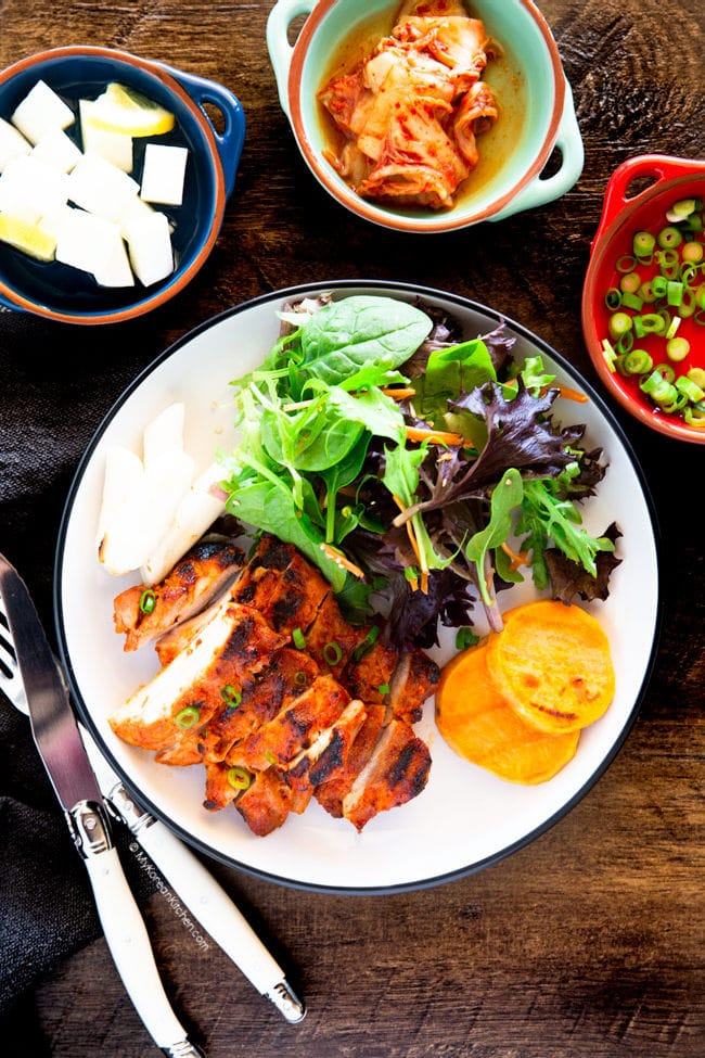gochujang chicken served with salad, kimchi, pickled radish